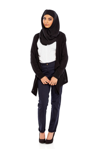 Portrait of a young Muslim woman in a head scarf standing over white background