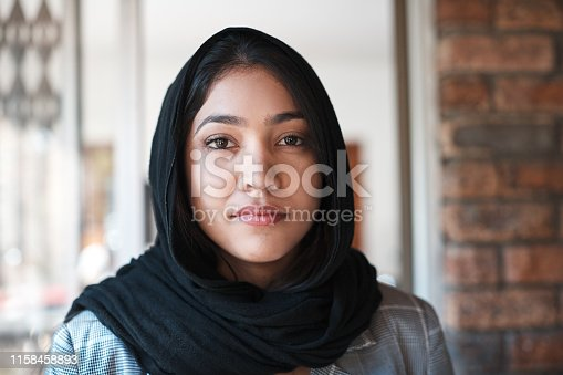 Young woman wearing a hijab standing at an entrance.