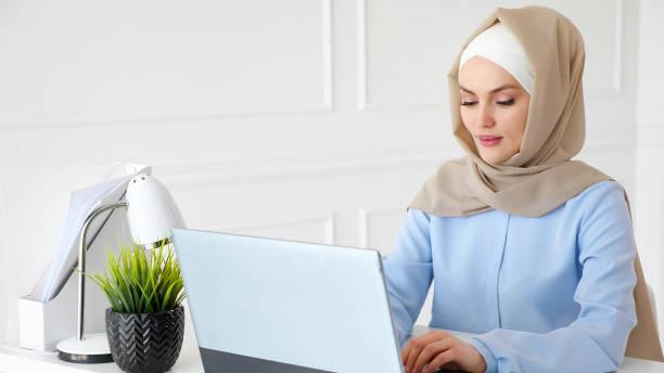 Junge muslimische Frau tippt auf Laptop im Büro – Foto