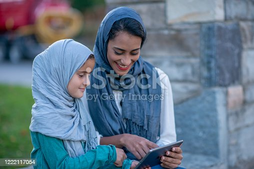 Young Islamic woman using her portable phone.
