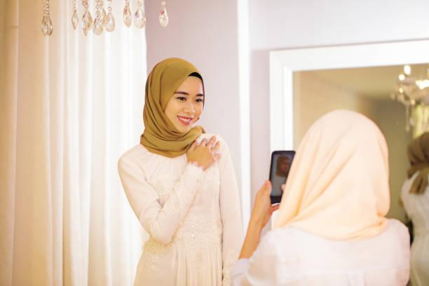 junge muslimische frau fotografieren ihre freundin ein hochzeitskleid anprobiert - hochzeitskleider online stock-fotos und bilder
