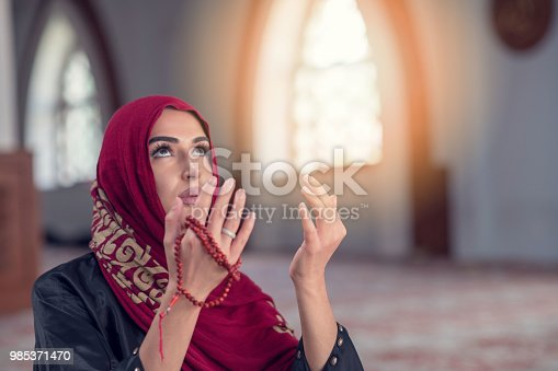 istock Young muslim woman praying with rosary in mosque 985371470