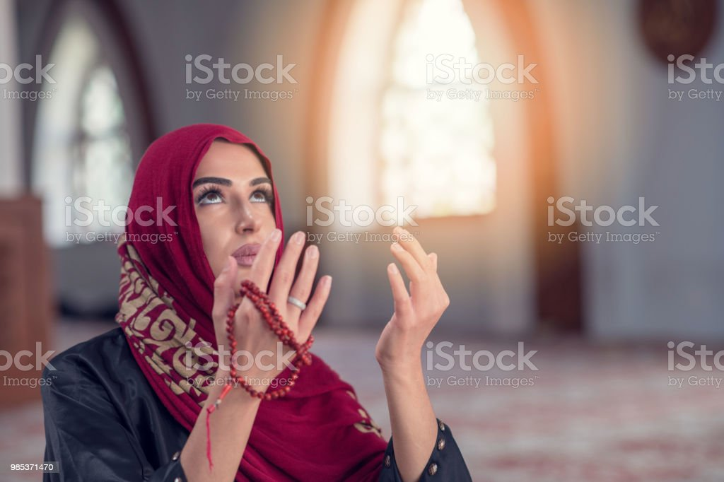 Young muslim woman praying with rosary in mosque stock photo