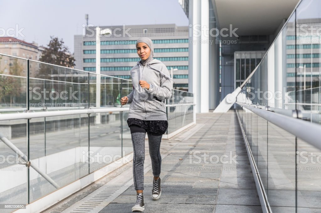 Young muslim woman ready to running in the city stock photo