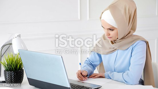 istock Young muslim woman student in hijab is doing her homework writing and drawing table on paper using laptop. 1149063932