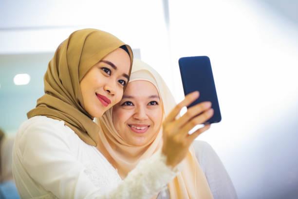 junge muslimische frau ein selbstporträt mit ihrer freundin in den brautladen nehmen - hochzeitskleider online stock-fotos und bilder
