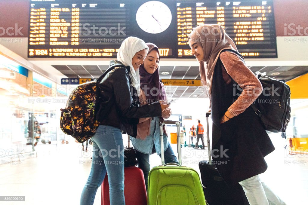 Young muslim women at train station leaving for a journey stock photo