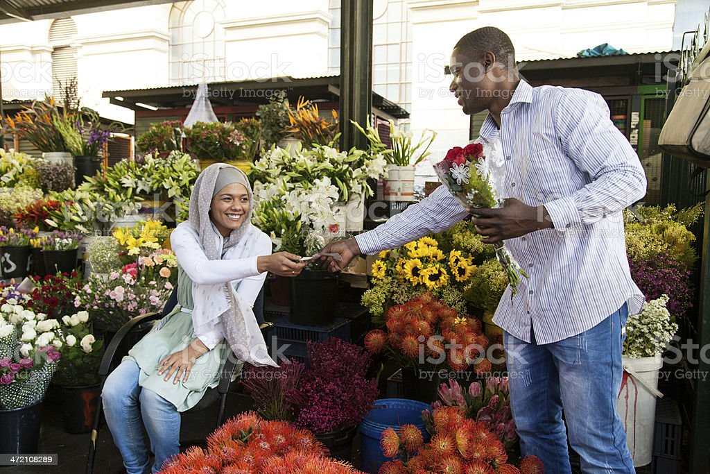 Young muslim women selling flowers to an african male. stock photo