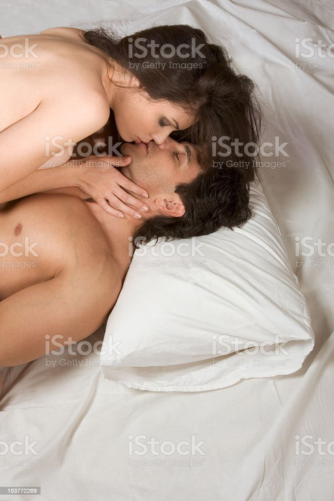 Young naked Man and woman making love in bed - Stock image .