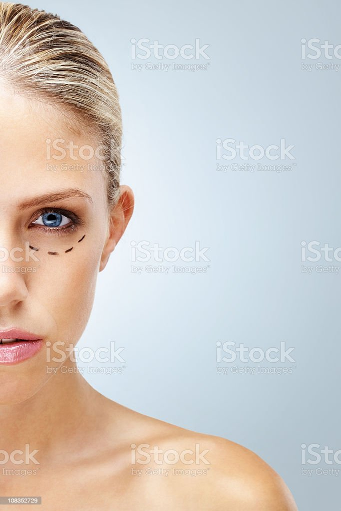 Young naked woman with markings below eye - copyspace royalty-free stock photo