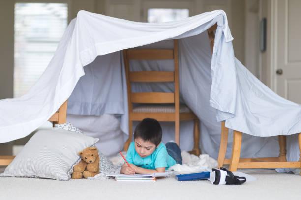 ung native american boy drar i sitt skissblock under sin filt fort i vardagsrummet - fort bildbanksfoton och bilder