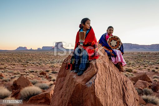 Young Navajo Brother and Sister in Monument Valley Posing on Red Rocks in front of the Amazing Mittens Rock Formations in the Desert at Dawn