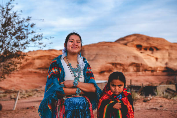 A Young Navajo Brother and Sister Who Live In Monument Valley, Arizona Native American sister and little brother posing for photographs in their native costumes navajo sandstone formations stock pictures, royalty-free photos & images