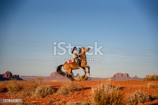 Young Navajo Teenage Boy Expertly Riding his Horse making it Buck in the desert in the Northern Arizona Navajo Reservation in Monument Valley Tribal Park