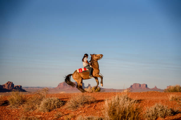Young Navajo Teenage Boy Expertly Riding his Horse making it Buck in the desert in the Northern Arizona Navajo Reservation in Monument Valley Tribal Park stock photo