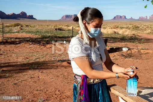 A teenage Navajo girl is putting a hand sanitizer on to protect her from Covid19