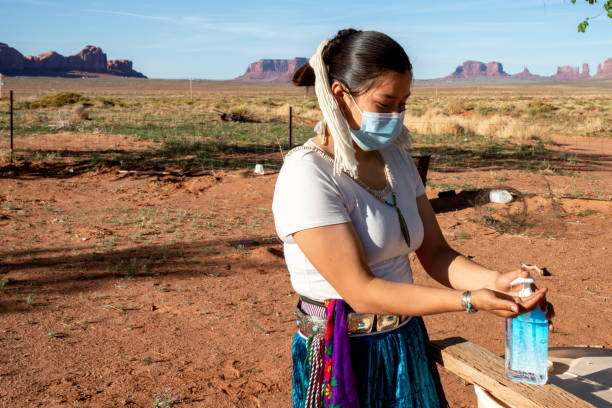 A Young Navajo Teenager Applying Hand Sanitizer To Help Protect Her From Coronavirus stock photo