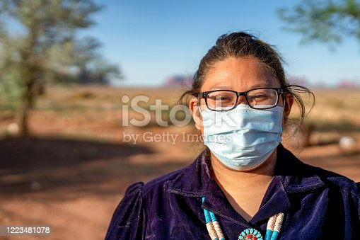 A native American teenager in her native costume wearing a face mask during the coronavirus, government shutdown