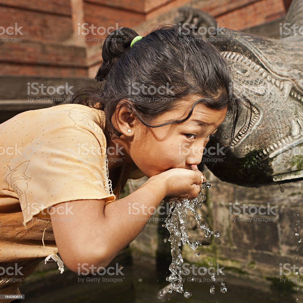 Young Nepali girl drinking from city fountain on Durbar Square royalty-free stock photo
