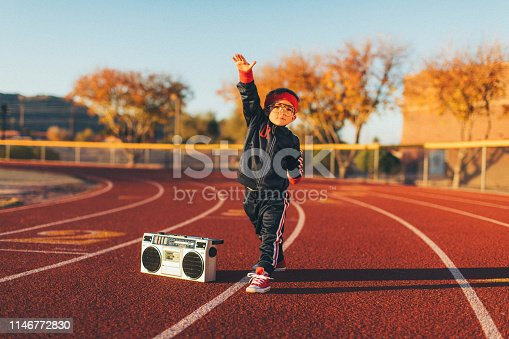 A young nerd boy dressed in a retro track suit and headband stands on the running track with his ghetto blaster ready to live a healthy lifestyle. He is eager to stretch and exercise while finding his inner chi. Image taken in Tempe, Arizona.