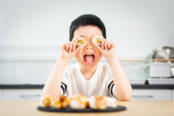 young nerd boy eating sushi - nerd boy eating stock photos and pictures