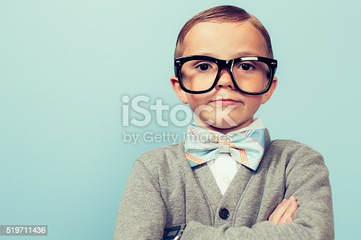 A young nerd boy with glasses sits with a blank expression on his face. He is wearing a bow tie and glasses and has an indifferent expression on his face. Retro styled