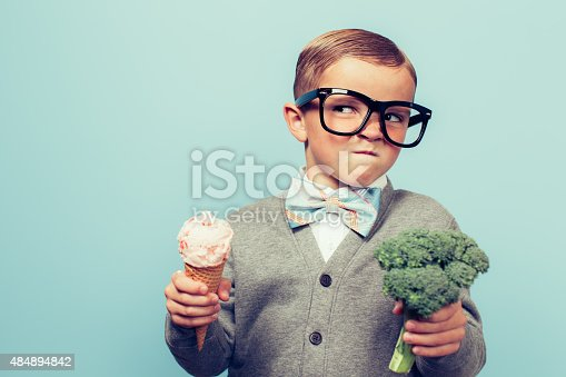 A young nerd boy with glasses is not sure whether to eat the ice cream cone or the broccoli. He is not sure which one is healthier.