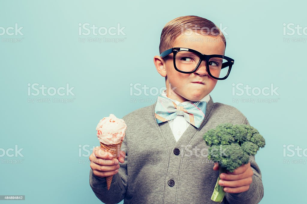 Young Nerd Boy Hates Eating Broccoli stock photo