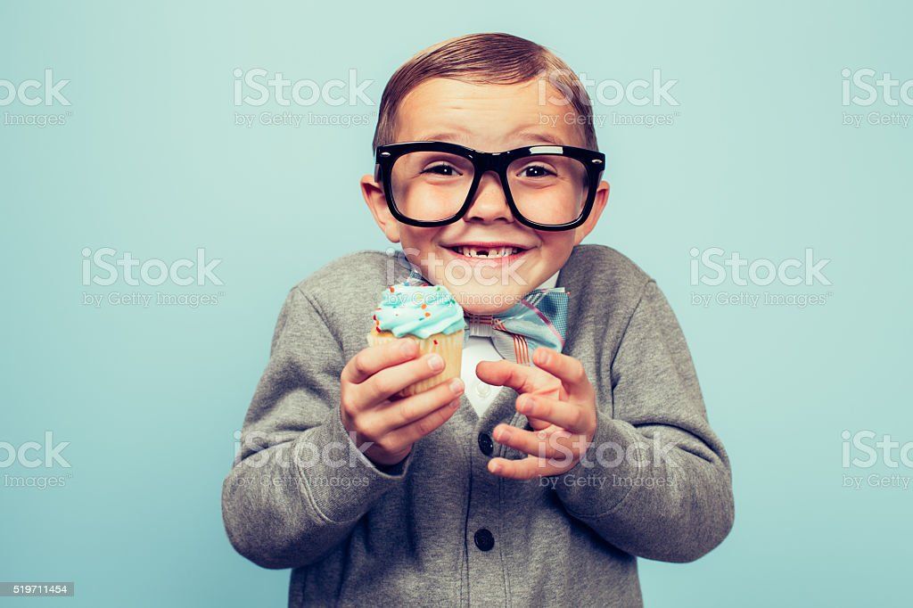 Young Nerd Boy Holding Cupcake in Hands stock photo