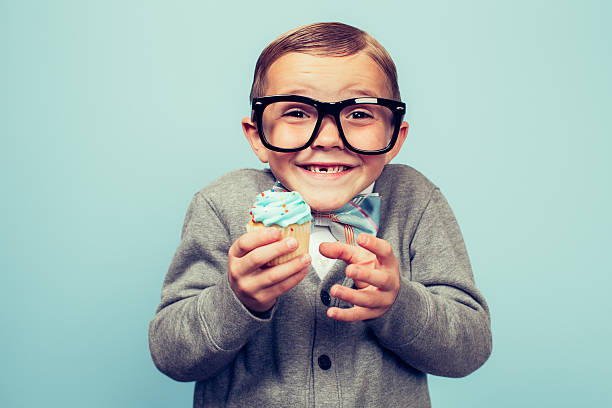 young nerd boy holding cupcake in hands - nerd boy eating stock photos and pictures