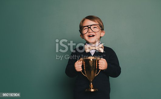 A young nerd boy wearing a bow tie and eyeglasses with a cheesy smile holds the winning contest trophy. He standing in class in front of a blackboard with his spelling bee trophy. He loves education and loves being smart.