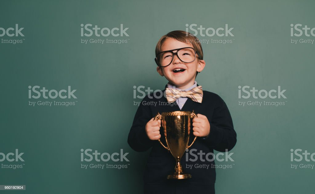 Young Nerd Boy Holding First Place Trophy stock photo