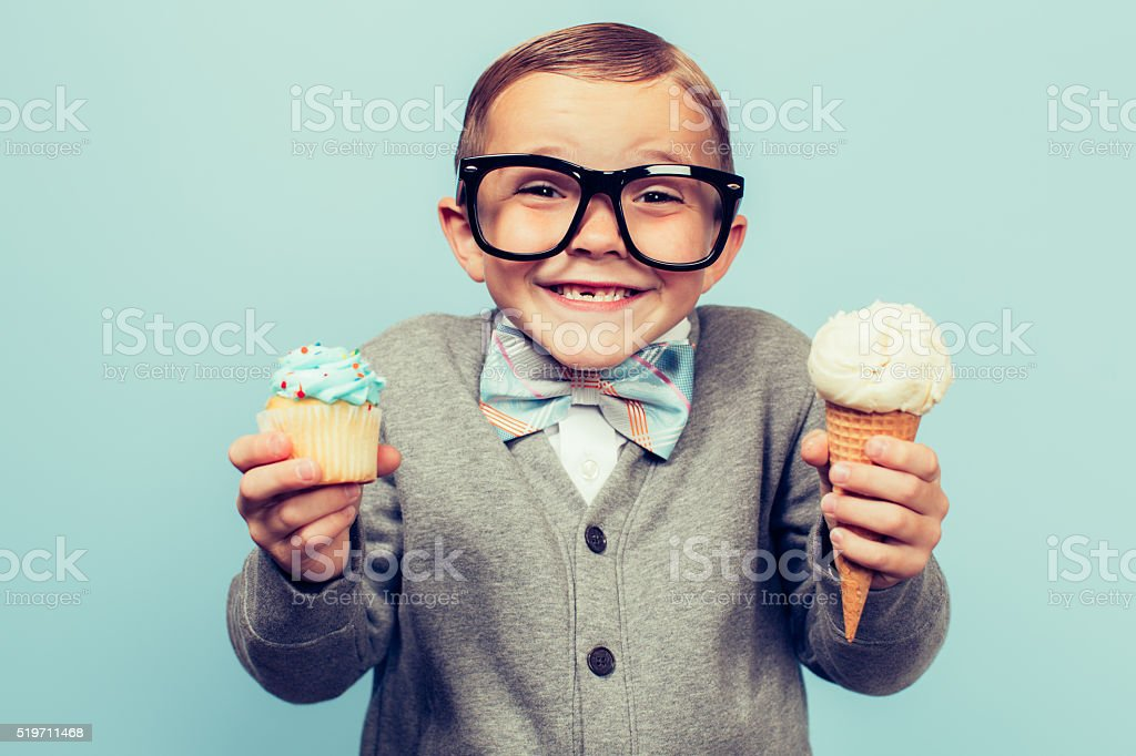 Young Nerd Boy Holds Ice Cream and Cupcakes stock photo