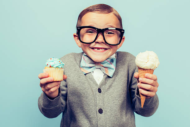 young nerd boy holds ice cream and cupcakes - nerd boy eating stock photos and pictures