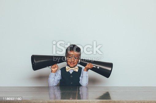 992091590 istock photo Young Nerd Boy Listening with Megaphones 1186931160