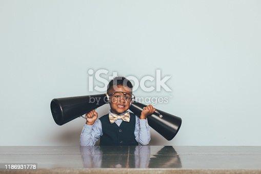 992091590 istock photo Young Nerd Boy Listening with Megaphones 1186931778