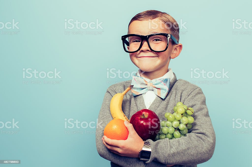 Young Nerd Boy Loves Eating Fruit stock photo