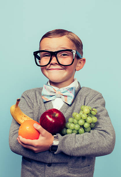young nerd boy loves eating fruit - nerd boy eating stock photos and pictures