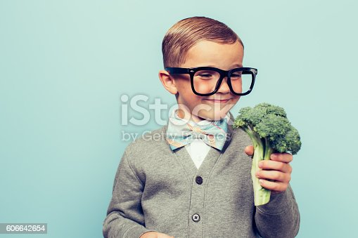 A young nerd boy with glasses is excited to eat his vegetables. He is dressed in bowtie and nice vest and glasses with a big smile at his broccoli.