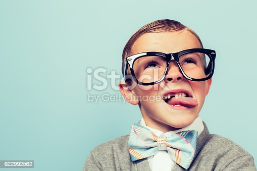 A young boy dressed as a nerd in bow tie and glasses makes a funny and bizarre face. He sits in a studio in front of a blue wall and is sticking his tongue out while looking up. Intelligent but weird.