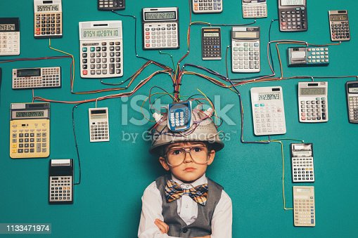 A young boy dressed as a nerd has a unique intelligence with numbers. He is a mathematics and numbers whiz, ready to solve any complex number problem. He is wearing a makeshift helmet and invention which uses many calculators to compute his solutions.