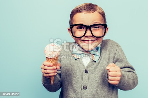 A young nerd boy with glasses loves eating sugary treats such as ice cream cones. He is smiling broadly and is excited to eat junk food. Retro styled