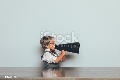 A young nerd boy dressed in bow tie, vest and wearing eyeglasses, holds and yells through a megaphone trying to get someone to listen to him. He sits at a table trying to get his message across to others.