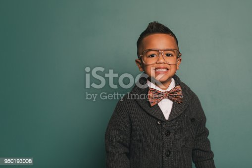 A young nerd boy wearing a bow tie and eyeglasses makes a toothy smile at the camera. He is sitting in class in front of a blackboard ready to learn at school. He loves education and loves being smart.