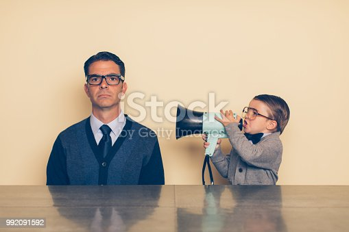 istock Young Nerd Boy Yelling at Dad through Megaphone 992091592