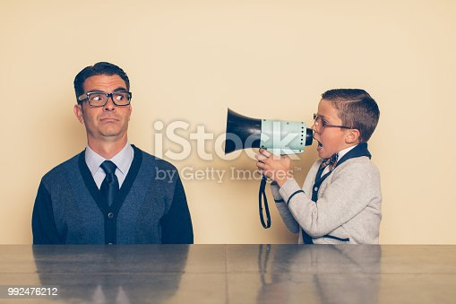 992091590 istock photo Young Nerd Boy Yelling at Dad through Megaphone 992476212