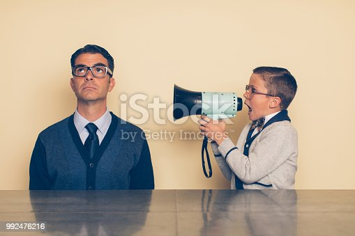 A young nerd boy in eyeglasses and a bow tie is yelling at his dad through a megaphone. His dad is looking up at the ceiling and ignoring what the son is saying. The son is frustrated with his dad because he won't listen as there is a generation gap.