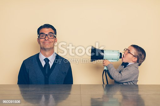 992091590 istock photo Young Nerd Boy Yelling at Dad with Megaphone 992091506