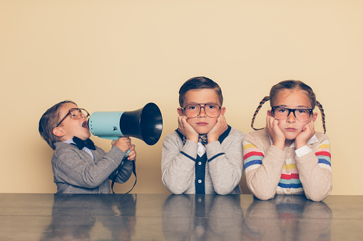 A young boy in glasses and a nerd outfit is shouting at his siblings through a megaphone. The big brother and big sister are looking at the camera with an annoyed look on their faces while plugging their ears. The little brother is bossing his older siblings around.