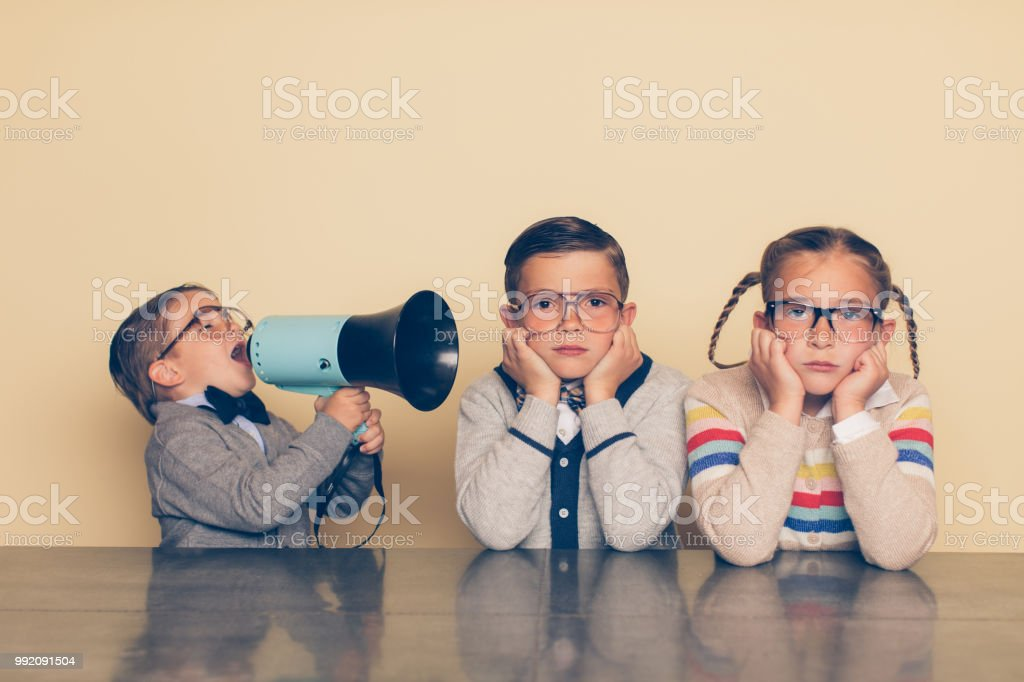 Young Nerd Boy Yelling at Siblings with Megaphone stock photo